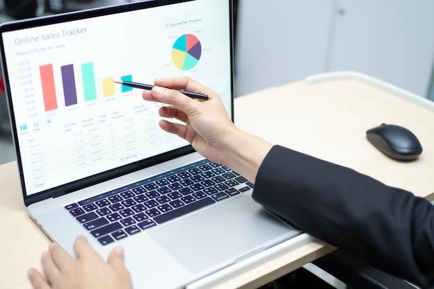 ラップトップでグラフを操作するアジアの会計士 Premium写真
