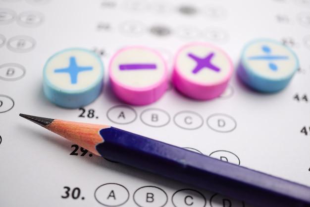 答えのシートの背景に数学記号と鉛筆。 Premium写真
