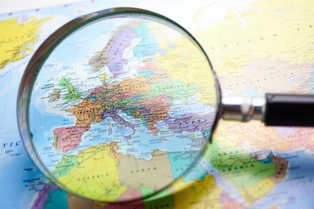 ヨーロッパ:世界地図の背景で拡大鏡。 Premium写真