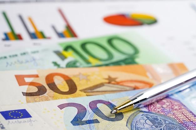 グラフグラフ背景紙の上のユーロ紙幣お金。 Premium写真