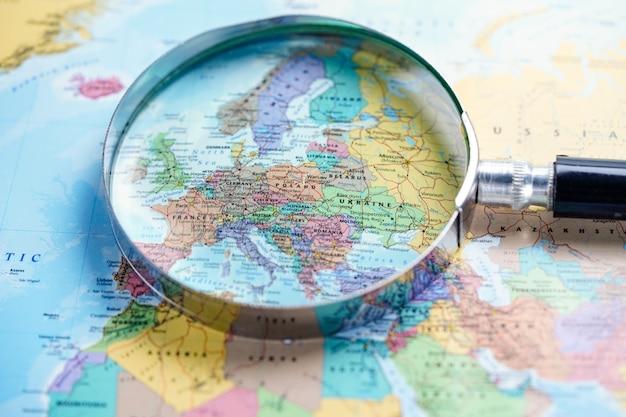 ヨーロッパの地球儀マップの背景に虫眼鏡。 Premium写真