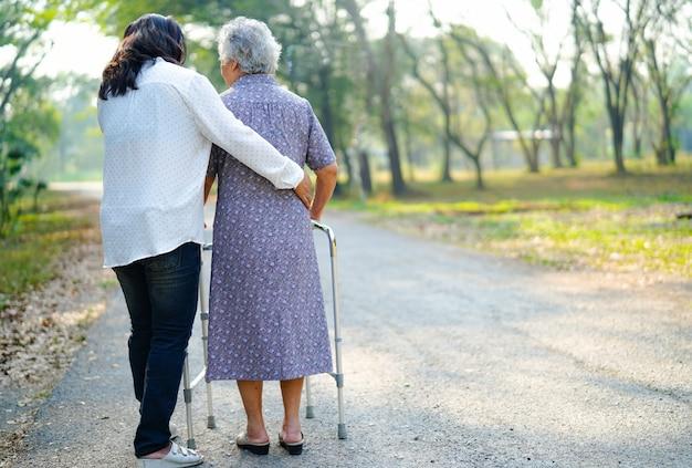 アジアの年配の女性が公園で歩きながらウォーカーを使うのを手伝ってください。 Premium写真