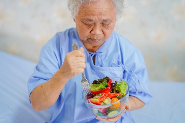 アジアのシニアまたは高齢者の老婦人女性患者の朝食の健康食品を食べる Premium写真