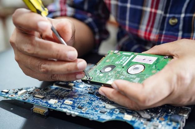はんだごてでハードディスク内部を修理する技術者。 Premium写真