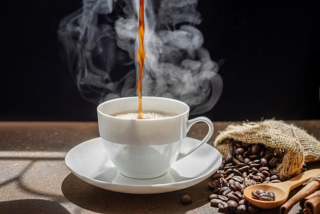 コーヒーをカップに注ぐことからの蒸気、新鮮なコーヒーのカップ Premium写真