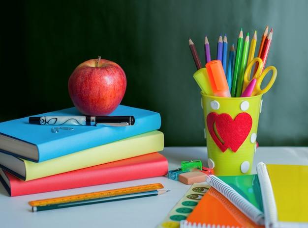 カラフルな学用品と背後にある赤いリンゴと緑の黒板と教師テーブルの詳細 Premium写真