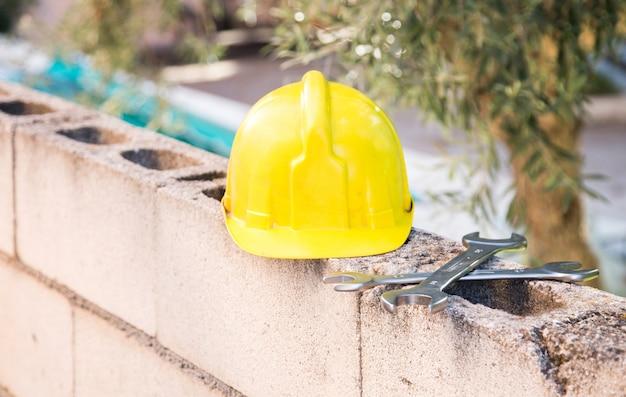庭の半分の壁に黄色のヘルメットと金属レンチの詳細 Premium写真
