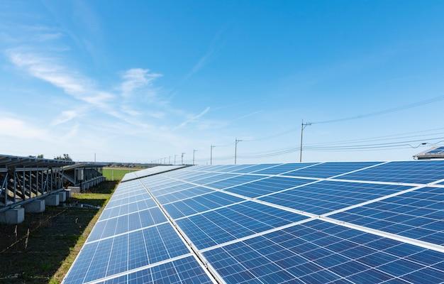Солнечные батареи (солнечные батареи) в солнечной ферме с голубым небом и солнечным освещением Premium Фотографии