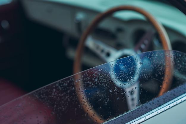 濡れている、雨が降っている、またはガラスに水滴が付いている運転手の横にある車のミラー Premium写真
