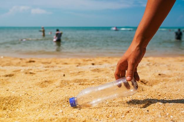 Убирать мусор на пляже Premium Фотографии