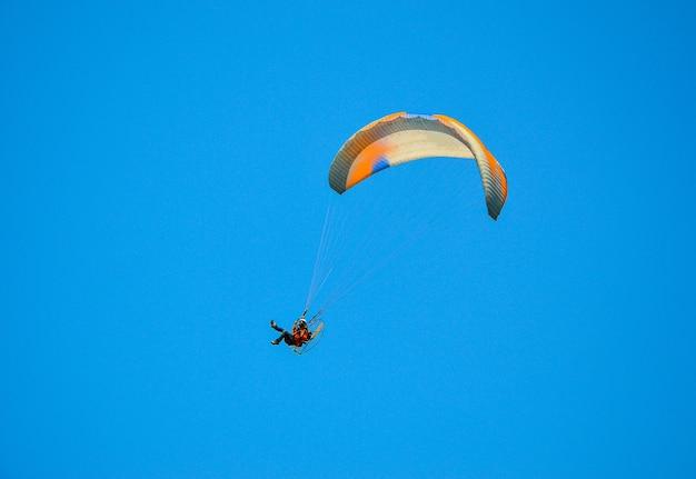 Парамотор, летящий в голубом небе Premium Фотографии