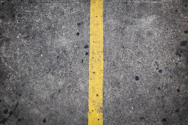 コンクリートの道路上の黄色の動線 Premium写真