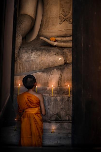 Новичок смотрит на большое изображение будды в церкви, чтобы помолиться за уважение религии. Premium Фотографии