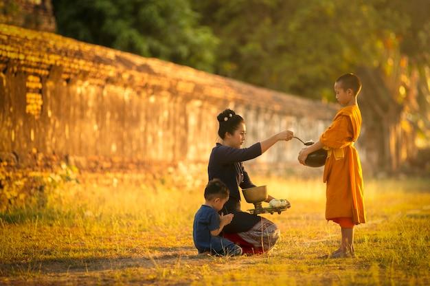 午前中は仏教徒は仏教の原則に従って功を奏し、僧侶が祝福する僧侶に食べ物を持ってくる。 Premium写真
