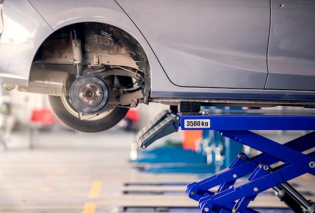 Автомобиль ждет замены запасного колеса в сервисном центре. Premium Фотографии