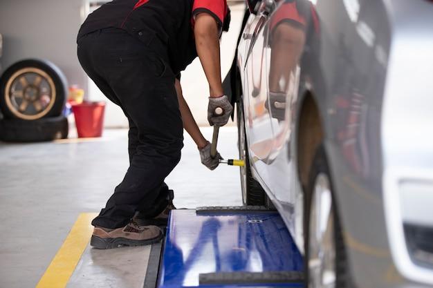 整備士は、タイヤセンターを使用する人のために車のタイヤを交換しています。 Premium写真