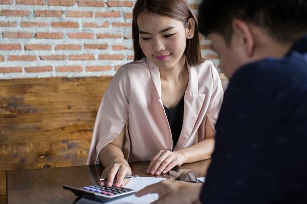 若いビジネスウーマンは、パートナーとビジネスを行うための収入支出を計算しています。 Premium写真