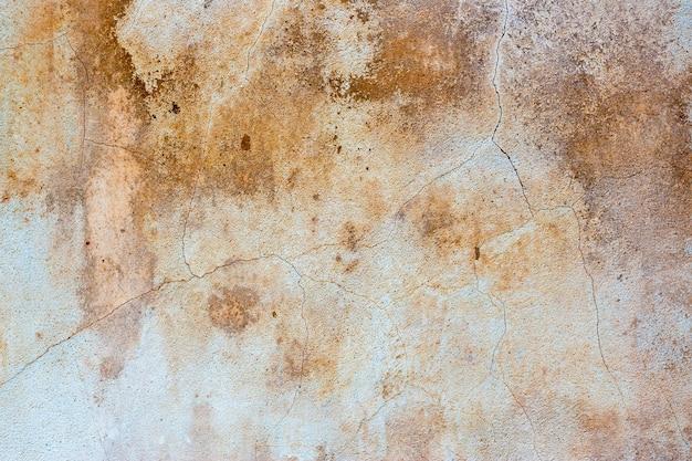 Старая, выветренная лепная стена, замусоренная коричневатыми пятнами и трещинами в качестве фона Premium Фотографии
