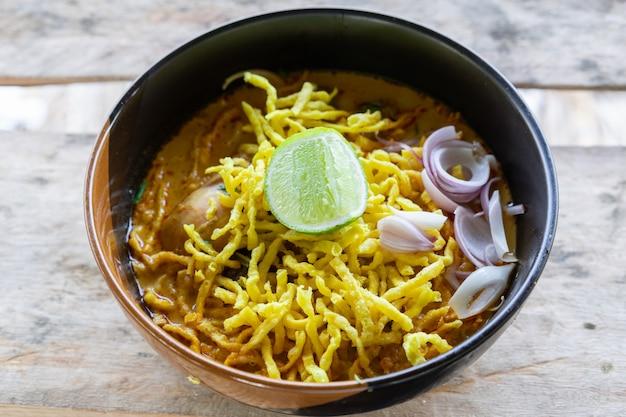 カレースープと伝統的なタイ北部のチキン(カオソイ)料理と麺のビュー Premium写真