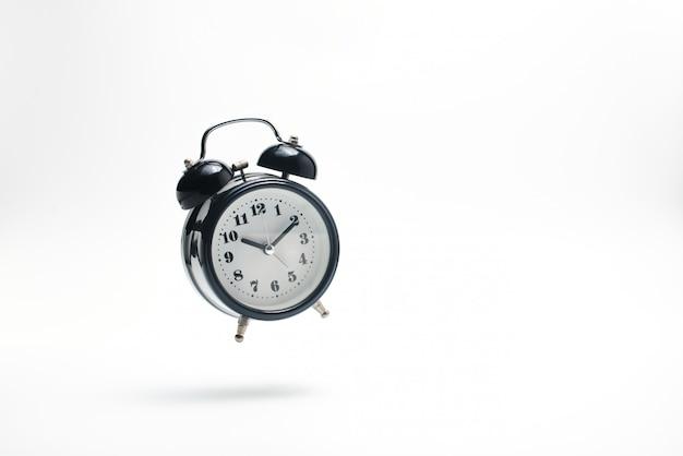 白に落ちる目覚まし時計。 Premium写真