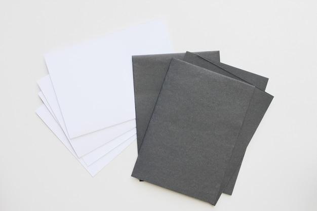 ビジネスの空白の黒と白のカードは、机の上に表示されます。 Premium写真