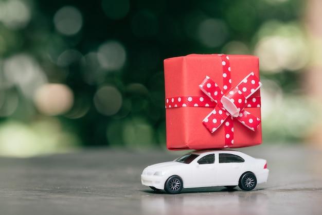 ギフトボックスを運ぶおもちゃの車。 Premium写真
