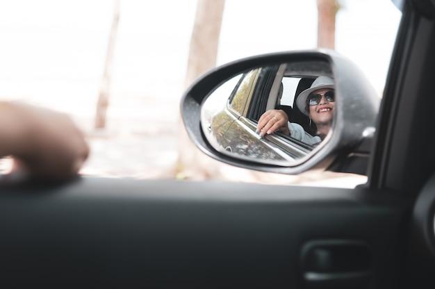 白いシャツのアジア女性はサイドミラーを見て、彼女の車、旅行の概念に坐っている間笑顔します。 Premium写真