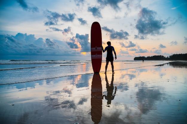 アジア人はビーチでサーフボードを運ぶ Premium写真