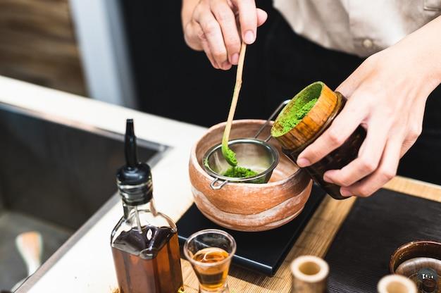 緑茶の飲み物を準備するバリスタ Premium写真