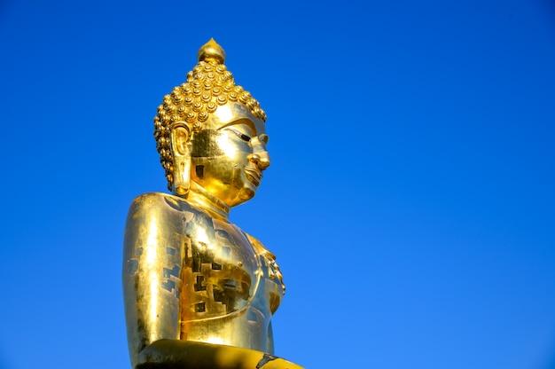 青い空を背景に古い黄金の仏像を閉じる Premium写真
