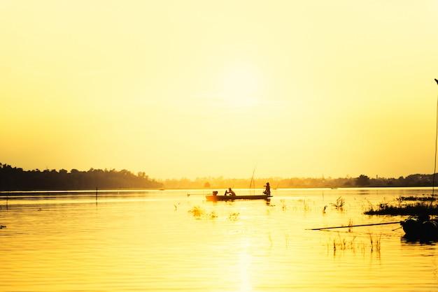 夕焼け空に対してマウンテンビューの湖で小型漁船のシルエット男 Premium写真