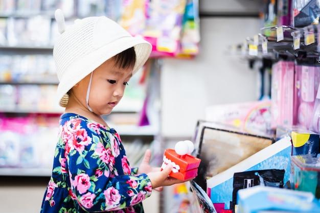 彼女の手で小さなおもちゃを見てバスケットとミニマートでのショッピングの甘いアジアの女の子 Premium写真