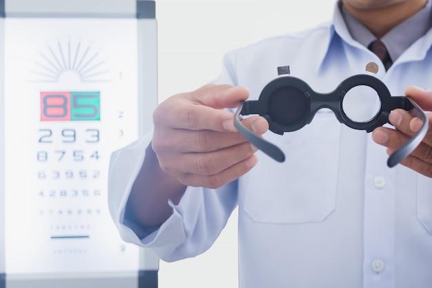 目を保持している眼鏡技師の男は患者に置くためのツールを検討しました Premium写真