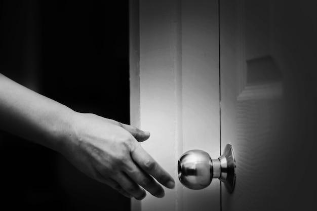 ドアのノブに届く女性の手を閉じて、白い色調のドアを開ける Premium写真