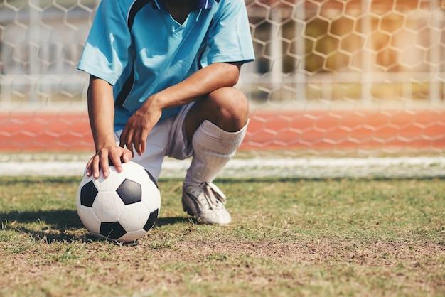 サッカーボールを持つ青チームコンセプトのサッカーフットボール選手 Premium写真