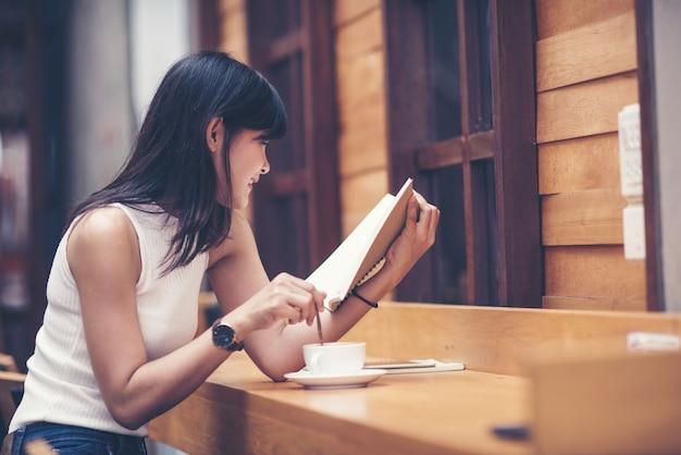 木製テーブルと読書をしている美しい女性 Premium写真