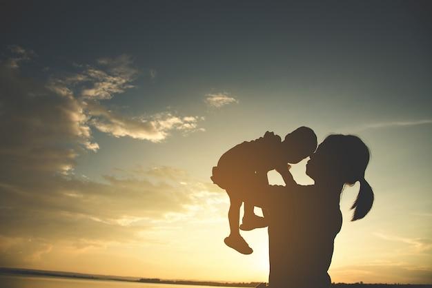 屋外で幸せな若い母親の母親のシルエット。 Premium写真