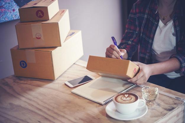 若い起業家、ティーンエイジャーのビジネスオーナーは自宅で仕事、配達のためのボックス Premium写真