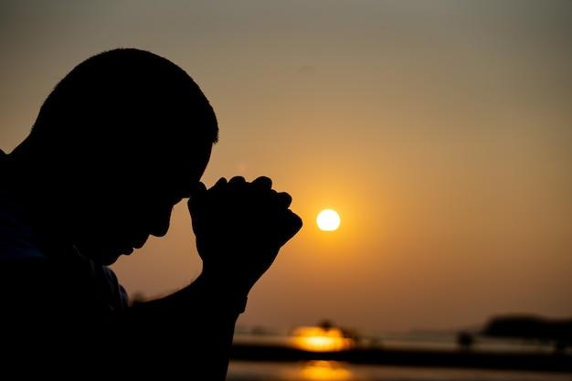 Тень человека молится и думает Premium Фотографии