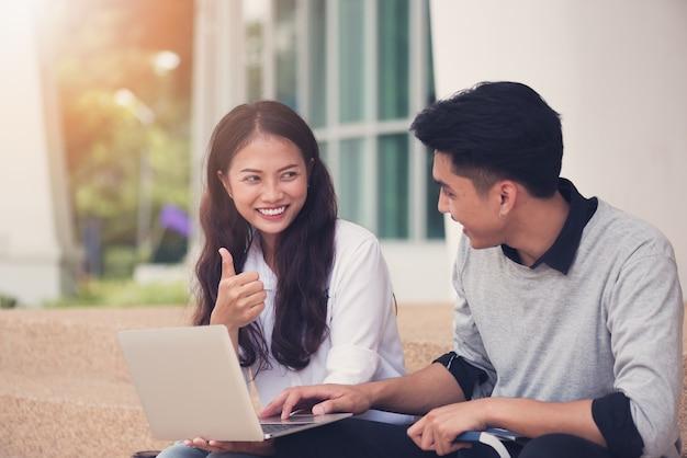 アジアのカップルの学生や同僚が階段に座って、ラップトップを使って笑う Premium写真