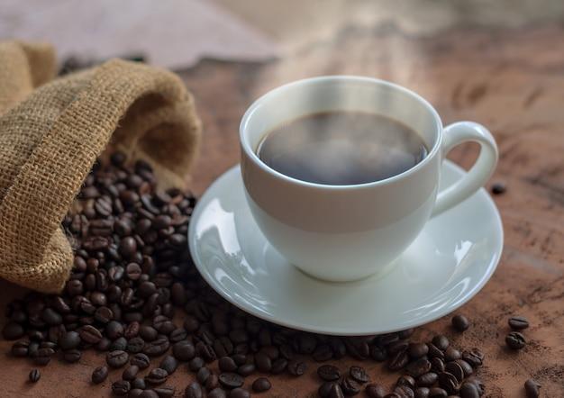 白いカップと木製のテーブルの上のコーヒー豆のコーヒー Premium写真