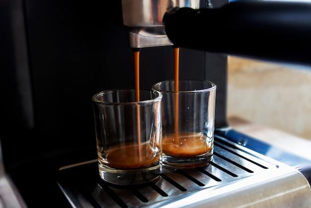 コーヒーはコーヒーマシンから流れています。 Premium写真