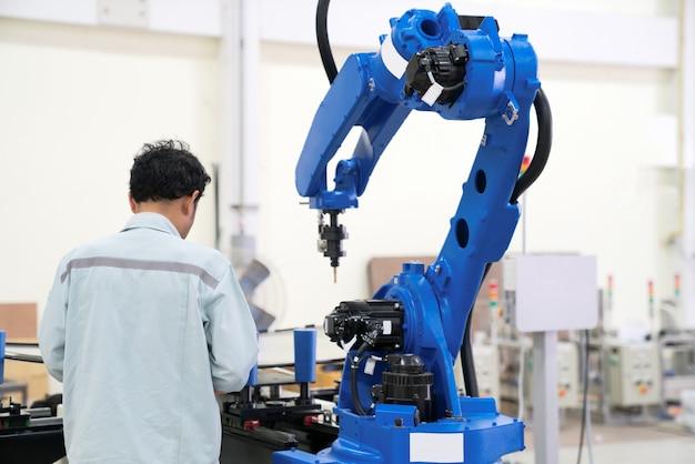 エンジニアの手は、スマートな工場の工業では、タブレット、重い自動化ロボットアームのマシンを使用して Premium写真