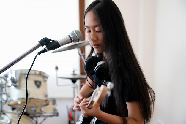 Закройте изображения девушки, играющей на гитаре. Premium Фотографии
