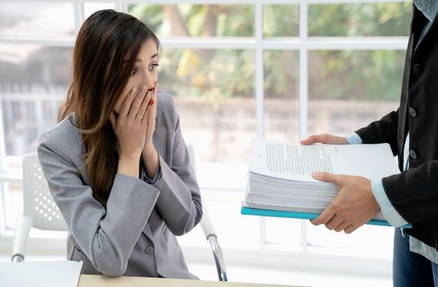 Снятый сотрясенной молодой коммерсантки смотря тревоженый в работе от ее босса. сюрприз бизнесвумен. Premium Фотографии