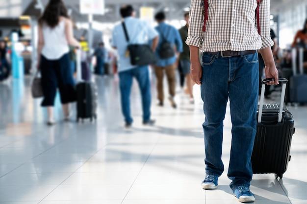 搭乗券をバックバッグに入れ、輸送ステーションでスーツケースを転がしている乗客。 Premium写真