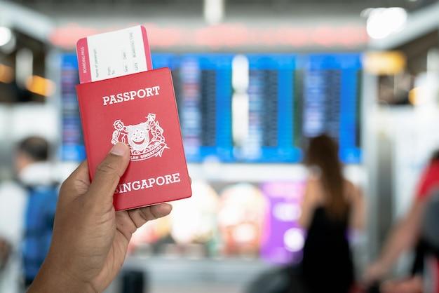 国際空港でパスポートとボーディングパスを持っている手。 Premium写真