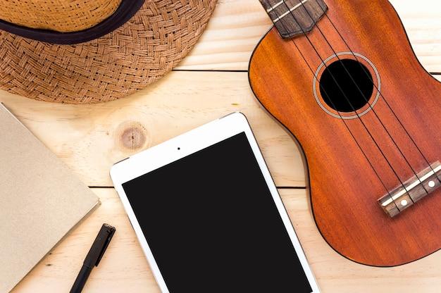 クローズアップウクレレ、タブレットコンピュータ、木の背景にノートブック。オーバーライト Premium写真