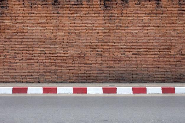 Дорога и старая красная кирпичная стена Premium Фотографии