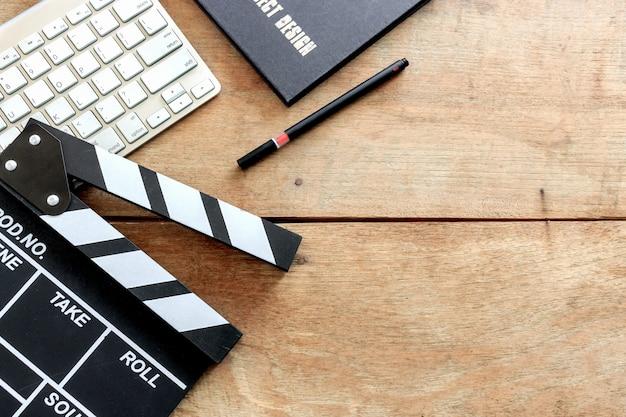 映画監督の机。カチンコ、本、木製のテーブルの上のデジタルカメラ Premium写真